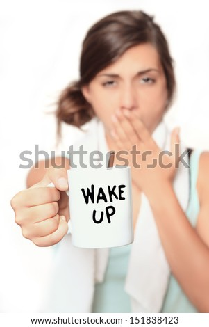 Wake up - young woman in the morning taking a coffee to help her get ready for the day - shallow depth and selective focus on cup - stock photo