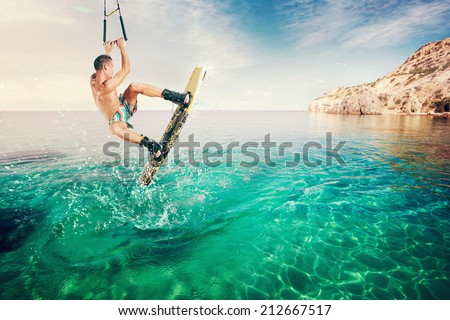 Wakeboarder making tricks on the sea. Wakeboarding. Water sports on the beach. - stock photo