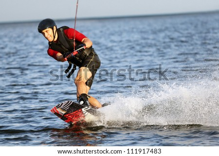 Wakeboarder surfing across the river - stock photo
