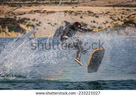 Wakeskater in a cable park doing a flip trick - stock photo