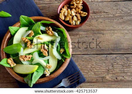 Waldorf salad with green apple, celery and walnuts in wooden bowl over rustic background - stock photo