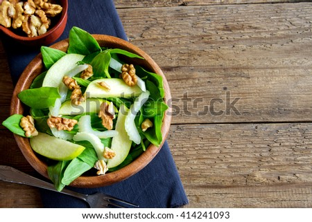 Waldorf salad with green apple, celery and walnuts in wooden bowl over rustic background with copy space - stock photo