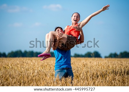 Walk a happy young couple on the nature outside the city. The guy carries the girl on sunset wheat field - stock photo