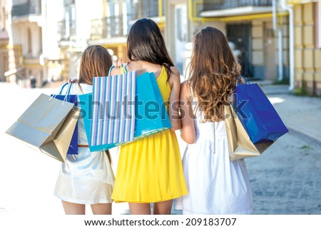 Walk shopping Three girls holding shopping bags and walk around the shops. Smiling girlfriends having fun together - stock photo