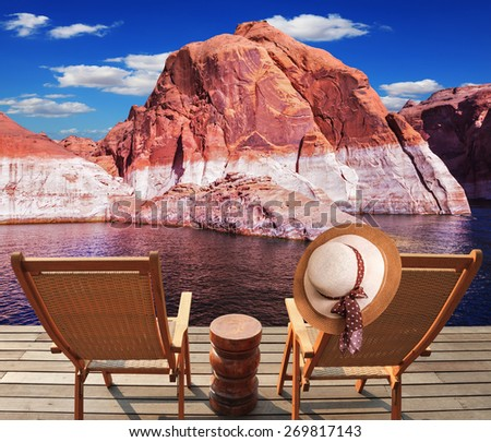 Walk to the tourist boat on Lake Powell on the Colorado River. At the stern of the vessel are two deck chairs. On the back of one hanging elegant ladies straw hat. - stock photo