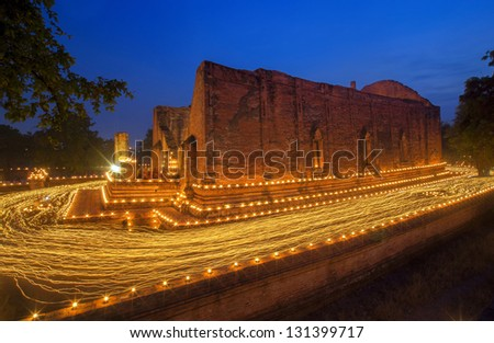 Walk with lighted candles in hand around a temple - stock photo