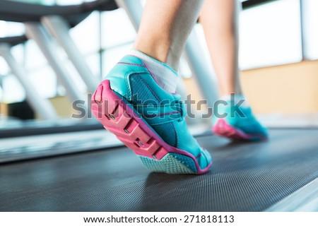 Walk. Woman's muscular legs on treadmill, closeup - stock photo