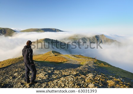 Walker above the clouds on Grisedale Pike, mountain in the English lake District. - stock photo