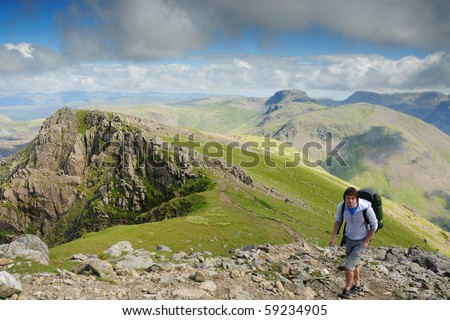 Walker on Pillar mountain in the English Lake District. Mountains in the background include Great Gable and the Scafell Range - stock photo
