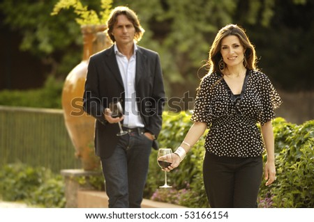 walking and holding glasses of wine - stock photo