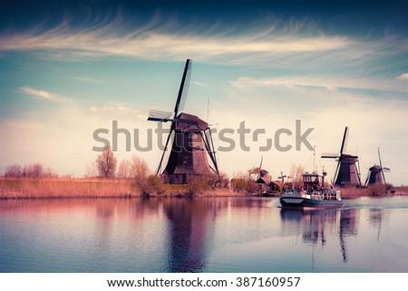 Walking boat on the famous Kinderdijk canal with windmills. Old Dutch village Kinderdijk, UNESCO world heritage site. Netherlands, Europe. Instagram toning. - stock photo