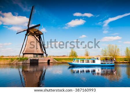 Walking boat on the famous Kinderdijk canal with windmills. Old Dutch village Kinderdijk, UNESCO world heritage site. Netherlands, Europe. - stock photo