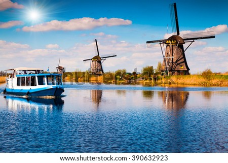Walking boat on the famous Kinderdijk canal with windmills. Old Dutch village Kinderdijk, UNESCO world heritage site. Netherlands, Europe. - stock photo