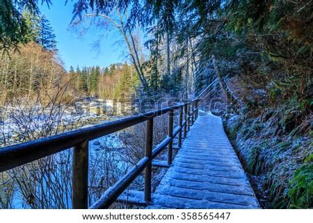 walking bridge by a stream in winter - stock photo
