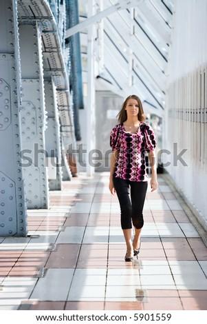 Walking girl. Modern bridge interior. - stock photo