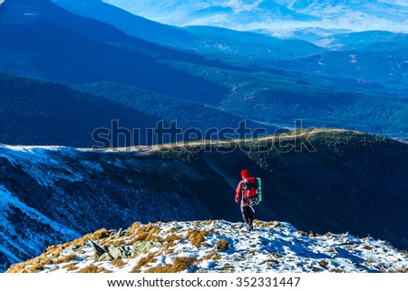 Walking Hiker in Red Jacket with Backpack on Snow Slope distant Mountain Ridges stacked on Background  - stock photo