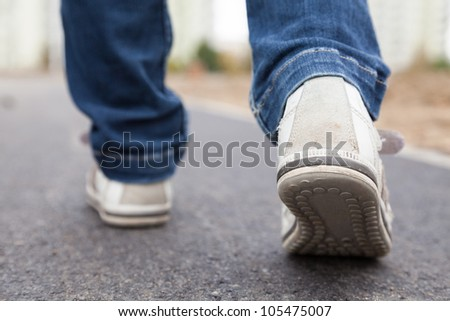 Walking in sport shoes on pavement in park - stock photo
