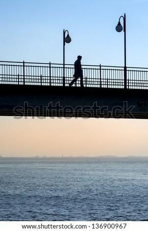 Walking man on pier during sundown, Miedzyzdroje, Poland - stock photo