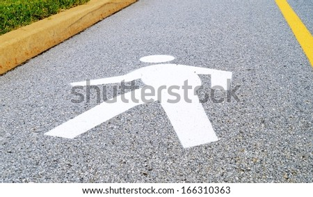 Walking Man Road Crossing Sign. Silhouette of a person painted on the street, a road sign marking a pedestrian walking lane. - stock photo