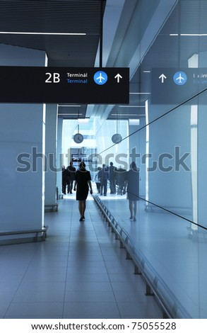 Walking men and woman in the airport - stock photo