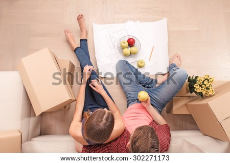 Walking on air. Top view of up of cheerful young couple sitting on near settee and holding apples while expressing positivity. - stock photo