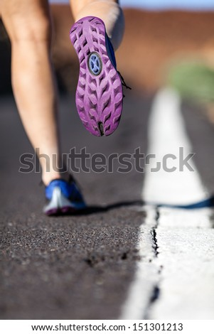 Walking or running legs on mountain road, adventure and exercising in summer nature. Hiker walk on asphalt sport shoe closeup. - stock photo