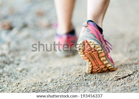 Walking or running legs on trail, adventure and exercising in mountains nature, runners sports shoe on dirt road - stock photo