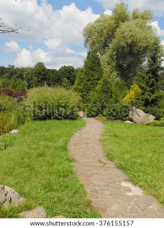 Walking path made of stones in a beautiful park area with lots of trees and shrubs - stock photo