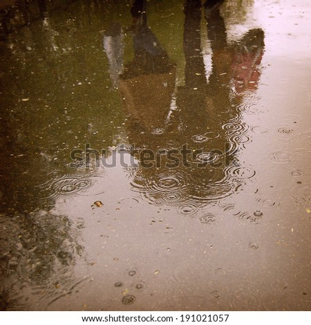 Walking people, reflection in the wet asphalt - instagram effect. Rainy day photo with retro filter. - stock photo