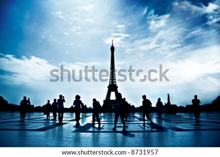 Walking people silhouettes in Paris. High contrast, blue tint and deep shadows. - stock photo