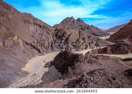 "Walking road to the ""Pillars of Amram"". Multi-colored mountains of Eilat, Israel. Warm day in January - stock photo"