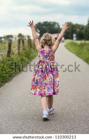 Walking toddler with her hands up in the air - stock photo