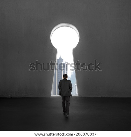 Walking toward to key shape door with skyscraper outside - stock photo