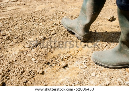 Walking with rubber boots on dry earth - stock photo