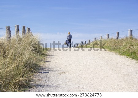 Walking with the dog in the dunes, Zoutelande, Netherlands - stock photo