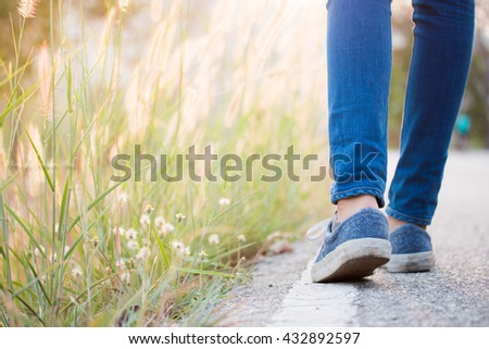 Walking women jeans and sneaker shoes - stock photo