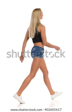 Walking young attractive blond woman in jeans shorts, sneakers and black shirt. Side view. Full length studio shot isolated on white. - stock photo