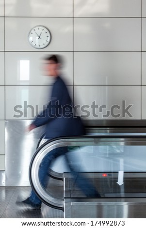 Walking young businessman on walkway in the airport - stock photo