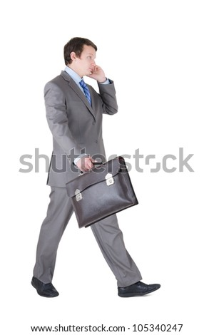 walking young businessman with briefcase isolated on white background - stock photo