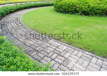 Walkway concrete worm in garden with plant and flower. - stock photo