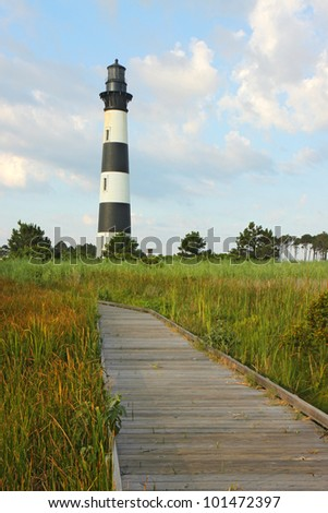 Walkway leading to the Bodie Island lighthouse over marshes of the Cape Hatteras National Seashore against white clouds and a blue morning sky vertical - stock photo