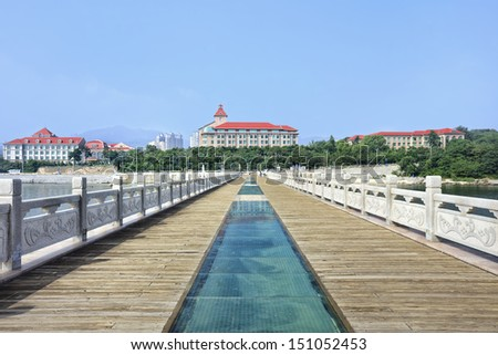 Walkway on a pier with stately buildings on the background, Yantai, China - stock photo