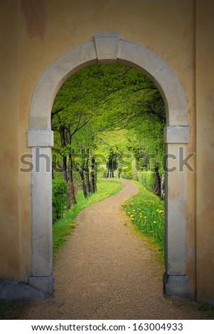 walkway through arched old door, mystical mood - stock photo