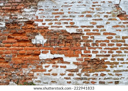 Wall built of red bricks with white painting partially destroyed - stock photo