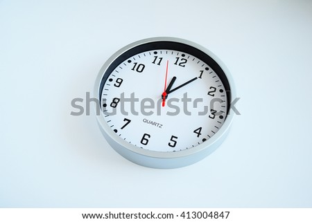 Wall clock isolated. Round white quartz wall clock. White wall clock on the white background. White face, black clockwise and numbers, red second hand, time on the clock is 12-05. 5 minutes on clock. - stock photo