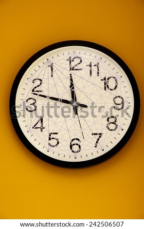 Wall clock with a net of lines and the order of the numbers inverted - stock photo