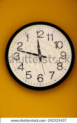 Wall clock with the order of the numbers inverted inside a net of lines. - stock photo