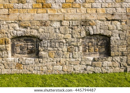 Wall made of natural sandstone rough fractured surfaces, laid as a brick. Stone wall background texture. Taupe cut block sandstone old wall with grass - stock photo