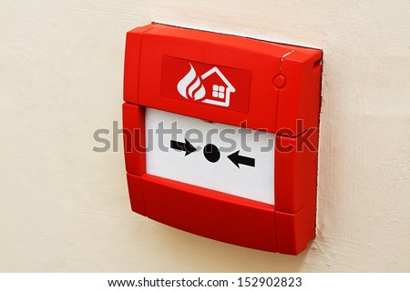 wall mounted Red fire alarm button used to activate warning systems in buildings - stock photo