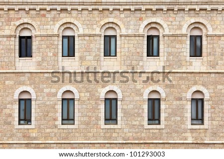 Wall of building made from Jerusalem stone with windows - stock photo
